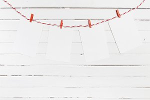 Blank paper or photo frames hanging on the red striped clothesline . On wooden background. Template for your text.