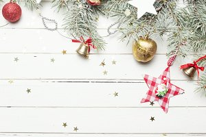 Christmas or New Year background: fur-tree branches, colorful glass balls, decoration and glittering stars on white wood, top view, copy space.