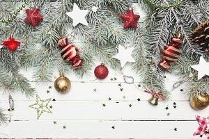 Christmas or New Year decoration background: fur-tree branches, colorful glass balls and glittering stars on white wooden background, top view, copy space