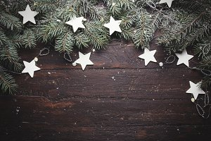 Christmas or New Year background: fur-tree branches, decoration and glittering stars on wood, top view, copy space