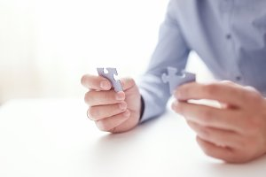 Businessman hands connecting jigsaw puzzle. Business solutions, success and strategy, learning concept. Close up photo with small dof