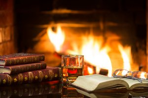 Glass alcoholic drink wine antique books in front warm fireplace.