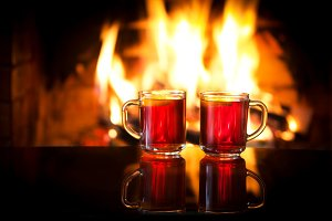 Hot drink mulled wine in front of warm fireplace.