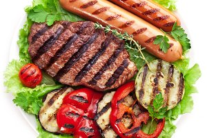 Grilled steak, sausages, vegetables.