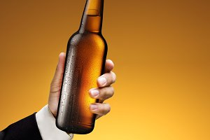 Bottle of beer in a man's hand on a yellow background.v