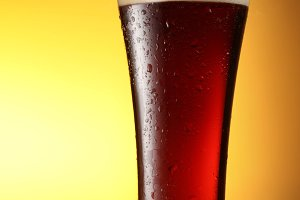 glass of dark beer on a yellow background