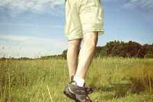 Man in shorts hiking in grass