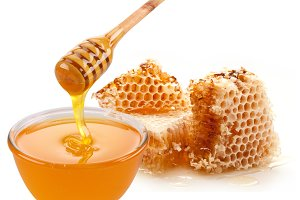 Pot of honey and wooden stick. Isolated on a white background.