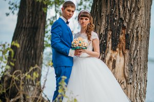 bride and groom standing on the background of trees