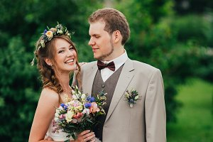 Young happy bride and groom on the background of greenery
