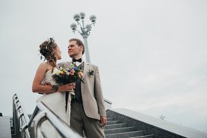young bride and groom on the background of the stairs