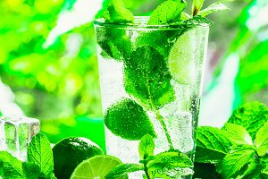 glass of mojito with mint and lime ice cube close-up