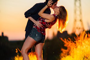 guy and the girl are standing  kissing in the sunset background