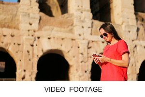 Woman with smartphone near Colosseum
