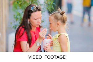 Mum feeds daughter ice-cream outdoor