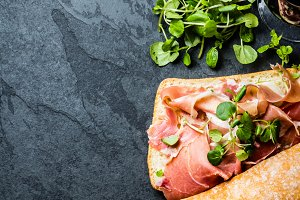 Ciabatta sandwich with jamon ham, arugula, slate background
