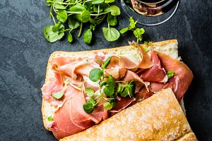 Ciabatta sandwich with jamon ham, arugula. red wine, slate background
