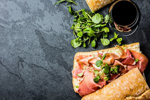 Ciabatta sandwich with jamon ham, arugula, red wine, slate background