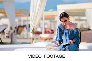 Young woman reading book on beach