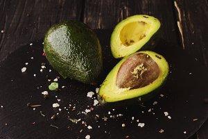 Green ripe avocado on a black stone coal, selective focus