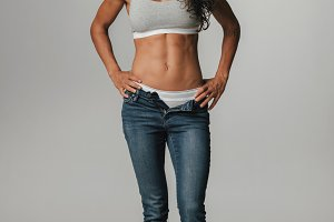 Calm woman in unzipped blue jeans