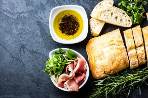 Ciabatta, pepper oil, jamon ham serrano, arugula, rosemary, slate background