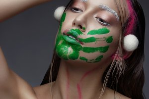 Beautiful Young Woman with Clean Fresh Skin pink makeup and  handprint with green paint