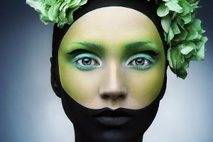 Girl with creative green and black and green make up and flowers