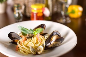 Italian spagetti with mussels and basil on a wooden table