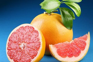 Ripe grapefruit with section on a blue background