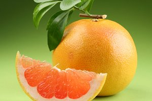 grapefruit with leaves  on a green background