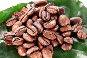 Coffee beans on a green leaf.