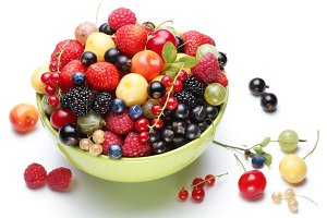 Colourful ripe berries in the bowl on a white background.