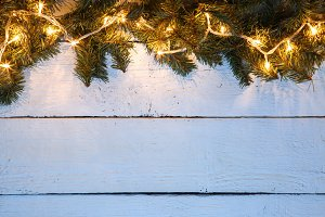 Christmas wooden background with evergreen branches and golden lighted garland