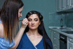 Stylist making make-up girl.