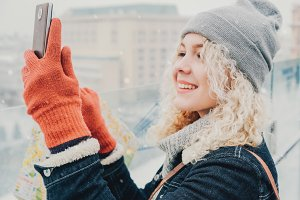 Young blond curly female do selfie