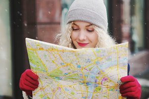blond curly female looking into map