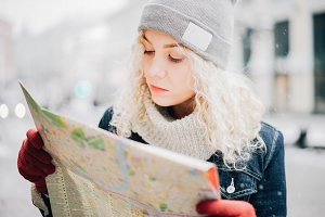 blond curly female tourist with map