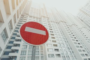 red stop road sign and skyscraper