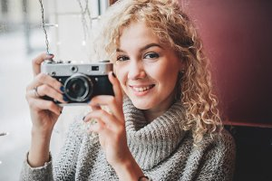 blond curly female with film camera