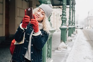 curly female tourist in warm clothes