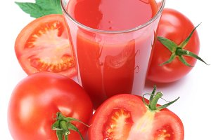 Full glass of fresh tomato juice and plants near it.