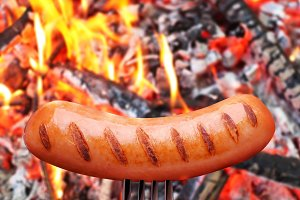 Sausage on a fork. In the background in bonfire.