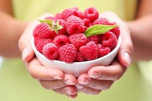 Crockery with raspberries in woman hands.
