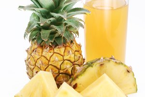 Full glass of fresh pineapple juice and pineapple fruit in the front.