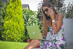 Busy woman calling at garden