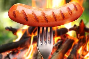 Sausage on a fork. In the background a bonfire in the forest.