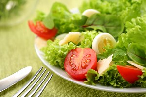 salad with eggs and tomatoes on a green background.