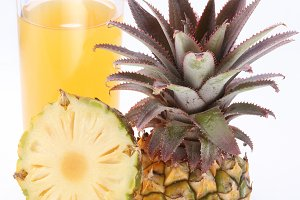 Full glass of fresh pineapple juice and cut pineapple fruit near.