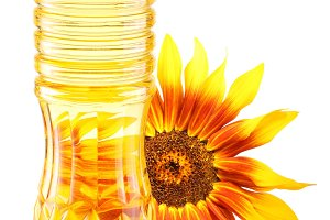 Cooking oil in a plastic bottle with sunflower on a white background.
